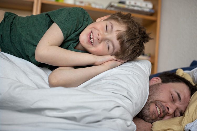 Portrait of happy friends sleeping on bed at home
