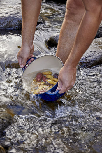 High angle view of man holding fish in water