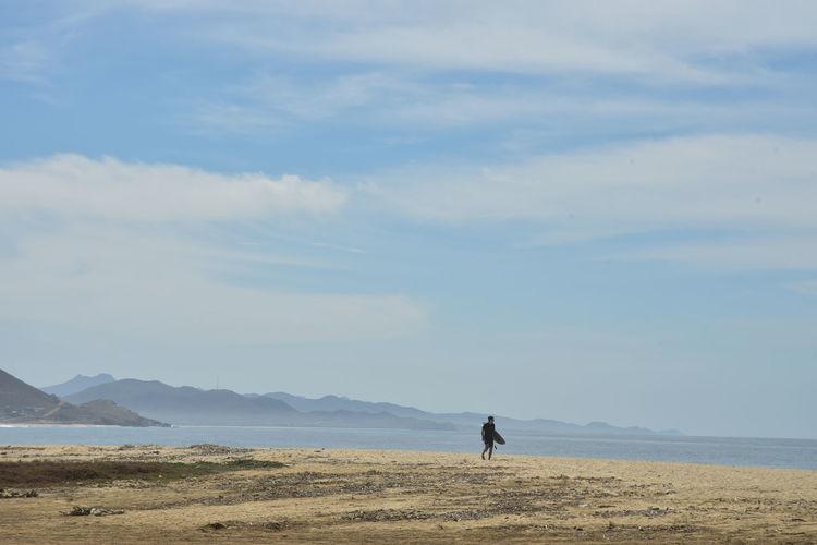 Surfer on seashore pacific coast beach