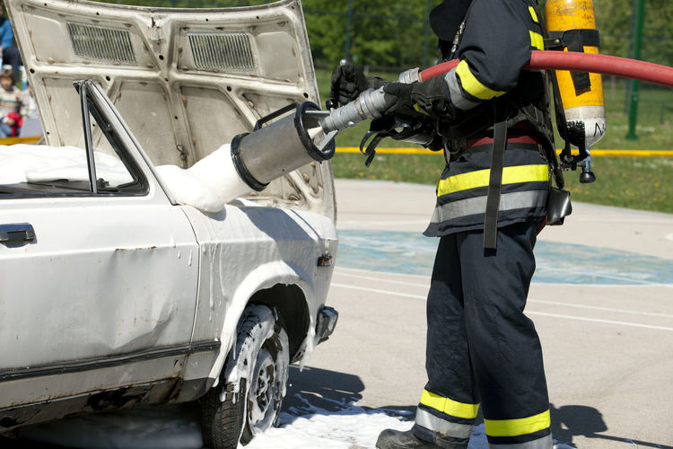 Low section of firefighter spraying water on car