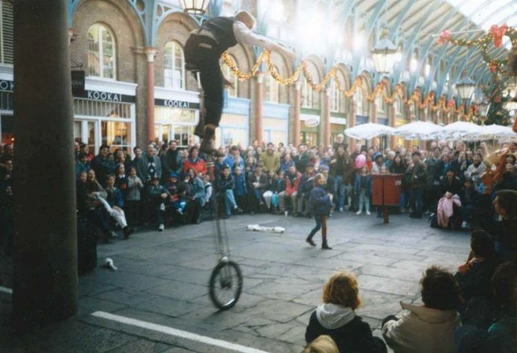 Unicycle Adult Architecture Building Exterior City City Life Crowd Group Of People Large Group Of People Men Motion Music Musician on the move Real People Sitting Street Travel Destinations Unicycle Tricks Women