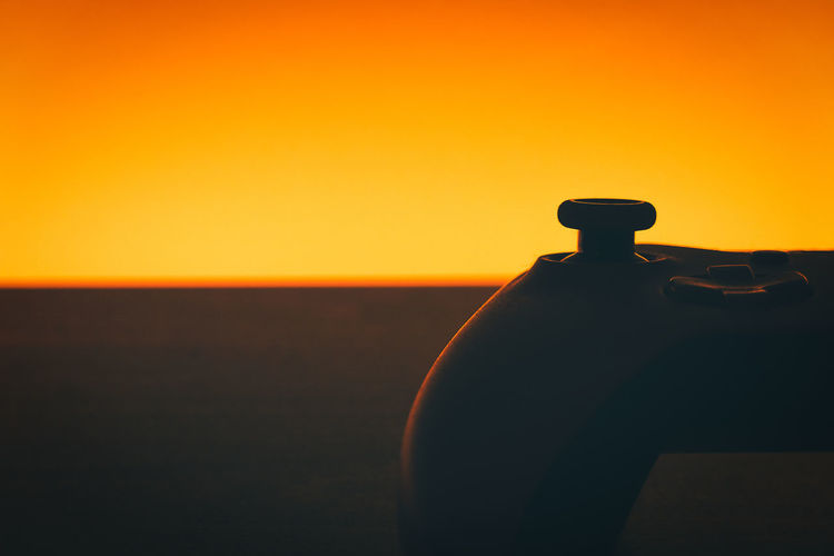 Close-up of silhouette tap against clear sky during sunset