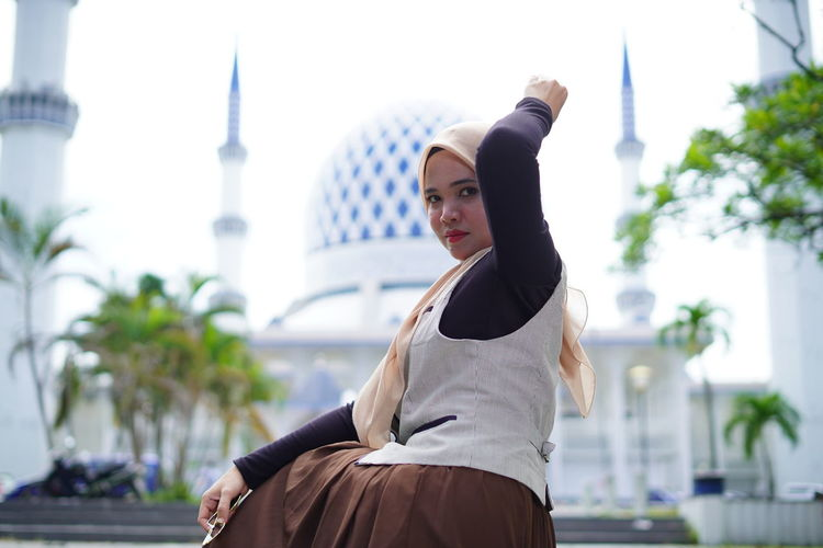 Young woman looking away while sitting on staircase against mosque