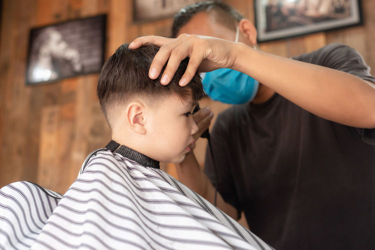 Close-up of boy getting haircut