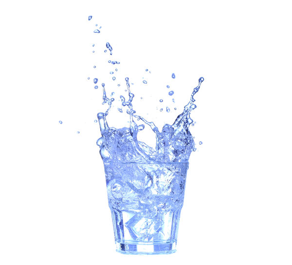 Close-up of water splashing on glass against white background
