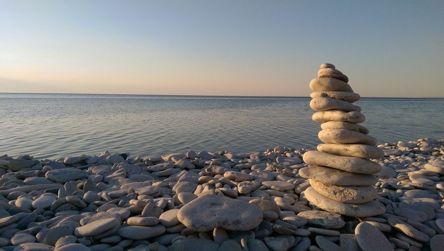 Stack of pebbles on shore at beach against clear sky during sunset