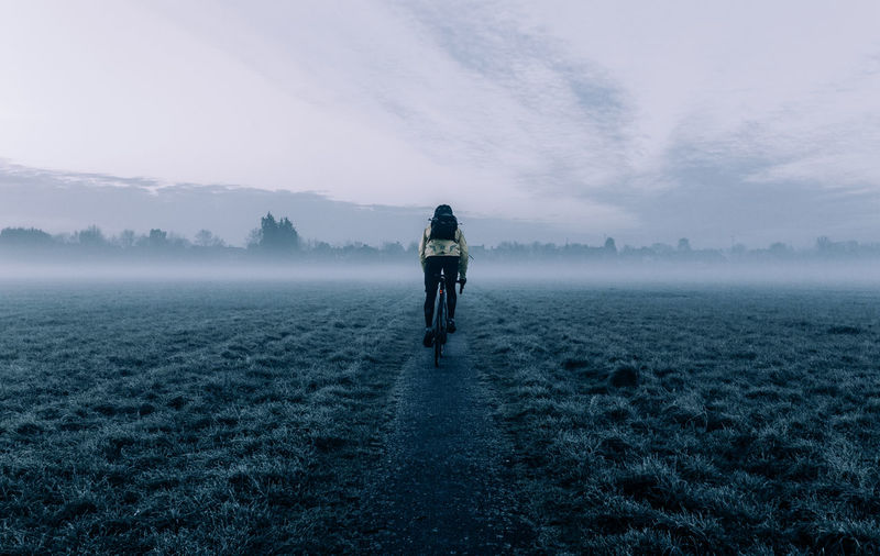 Rear view of man cycling on field against sky during foggy weather