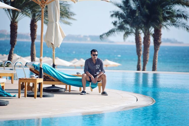 Full length of man relaxing on swimming pool at beach