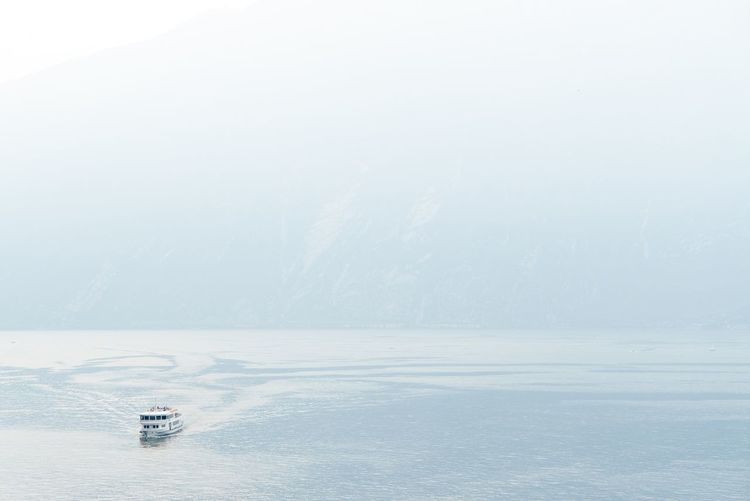 Minimalism Minimalobsession Lake Lake View Lakeview Italy Boat Ferry Ferryboat Sea And Sky Mountain From Above  Blue Dizzy Fog Foggy Morning Foggy Day