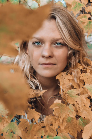 Portrait of beautiful young woman with leaves
