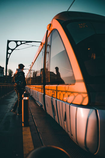Architecture Full Length Lifestyles Men Mode Of Transportation One Person Orange Color Outdoors Public Transportation Rail Transportation Railroad Station Railroad Station Platform Real People Rear View Sky Sunset Track Train Train - Vehicle Transportation Travel