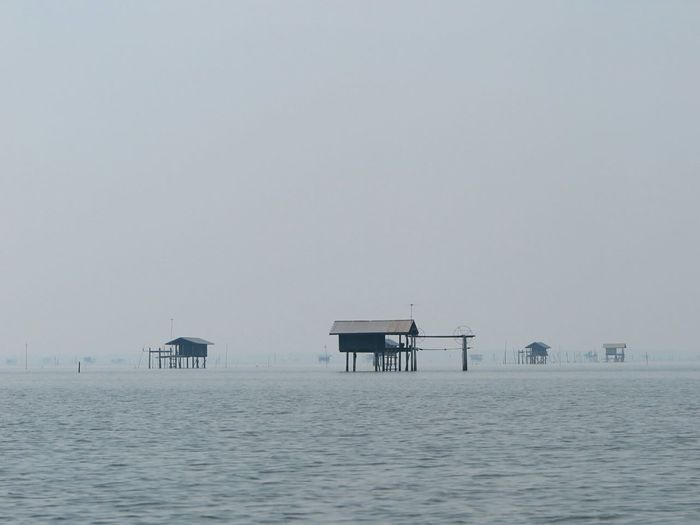 View of stilt structures in calm sea