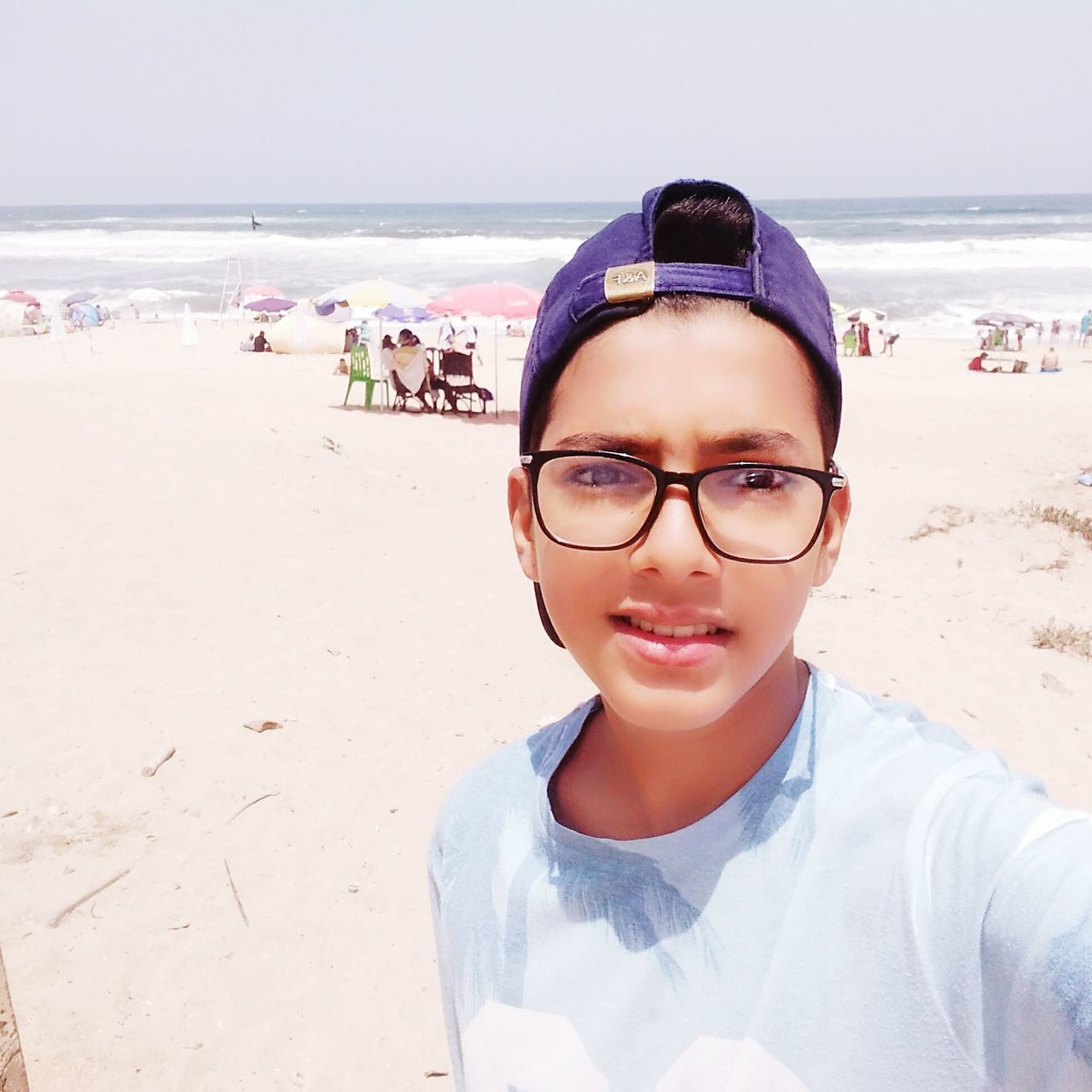 beach, real people, sea, eyeglasses, looking at camera, sand, leisure activity, shore, childhood, lifestyles, one person, portrait, outdoors, front view, vacations, day, nature, elementary age, boys, horizon over water, happiness, water, beauty in nature, sky