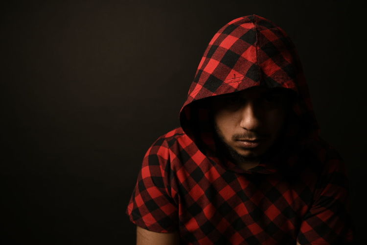 Close-up of man wearing checked pattern hooded shirt against black background