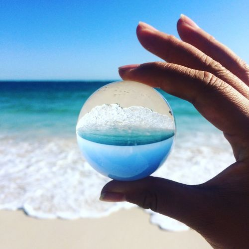 Close-Up Of Woman Holding A Sphere Against Sea