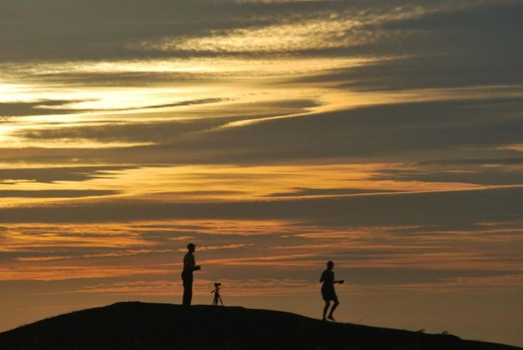 Silhouette Of Photographer With Model Taking Pictures During Sunset