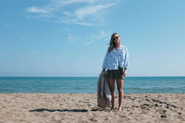 Young Woman Standing At Beach Against Blue Sky