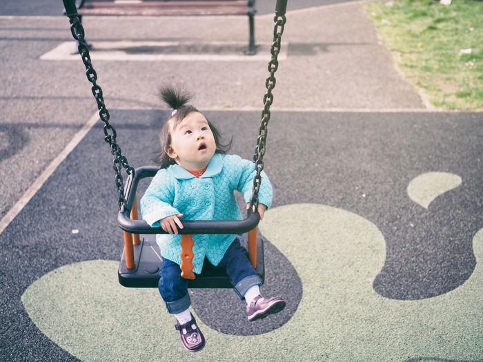 baby girl playing swing in outdoor playground Babies Only Baby Girl Childhood Day Full Length Happy Lookingup One Person Outdoors People Playground Sitting Swing