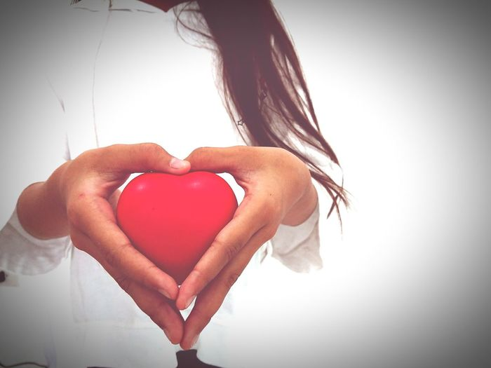 Close-up of woman holding heart shape over white background