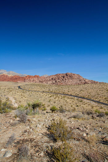 Scenic view of arid landscape against clear blue sky. red rock canyon, nevada
