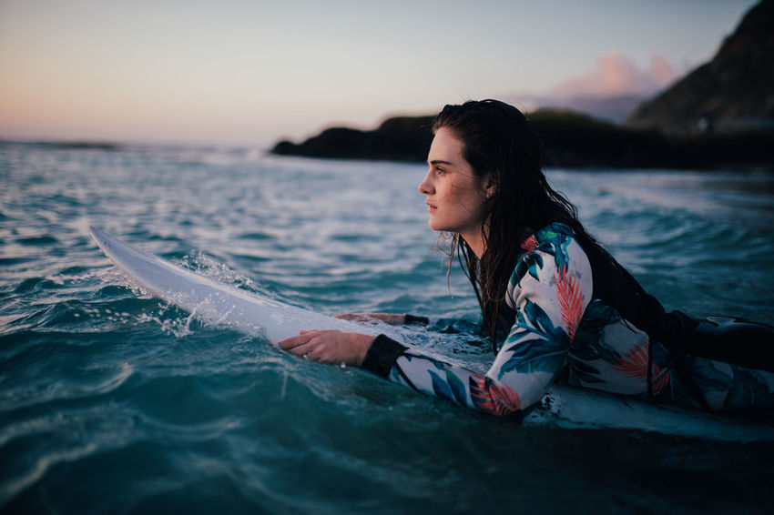 Water Sea Sunset Leisure Activity One Person Sky Nature Beach Adult Trip Vacations Young Adult Holiday Relaxation Land Beauty In Nature Outdoors Hair Hairstyle Contemplation Surfing Surfboard