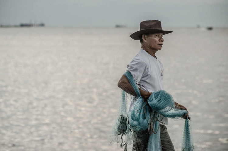 Senior fisherman with fishing net at sea Alone Casual Clothing Countryside Fisherman Fishing Net Folkways Hat Learn & Shoot: Working To A Brief Hobby Leisure Activity Life Lifestyles Man Nature Ocean People Portrait Sea Senior Senior Portrait Side View Standing Thailand Vintage Waiting