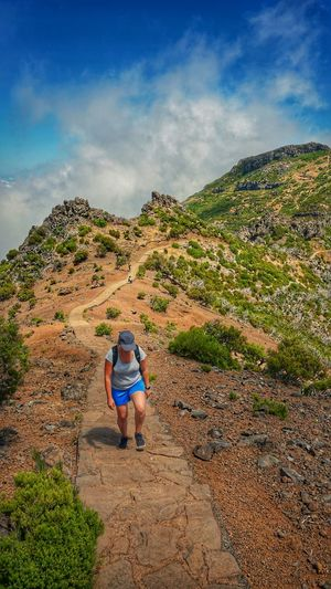 High angle view of woman hiking on mountain trail