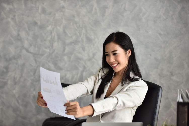 Businesswoman Business Business Person Holding Smiling One Person Paper Happiness Adult Corporate Business Document Women Indoors  Young Adult Waist Up Emotion Office Cheerful Activity Looking Paperwork