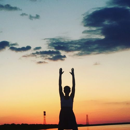 Silhouette woman exercising against sea during sunset