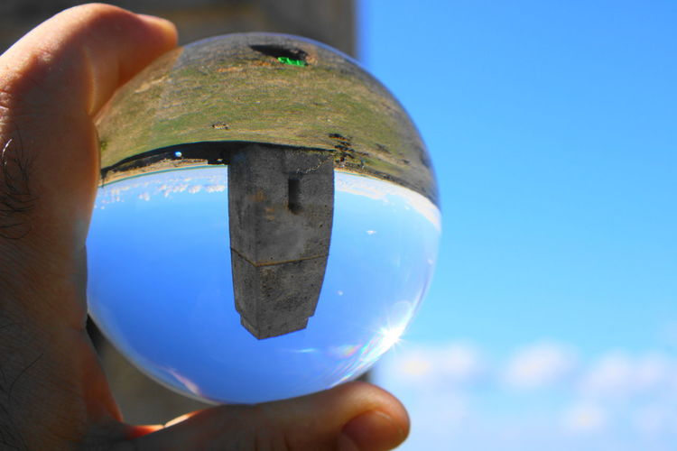 Cropped hand holding crystal ball with reflection on tower against blue sky