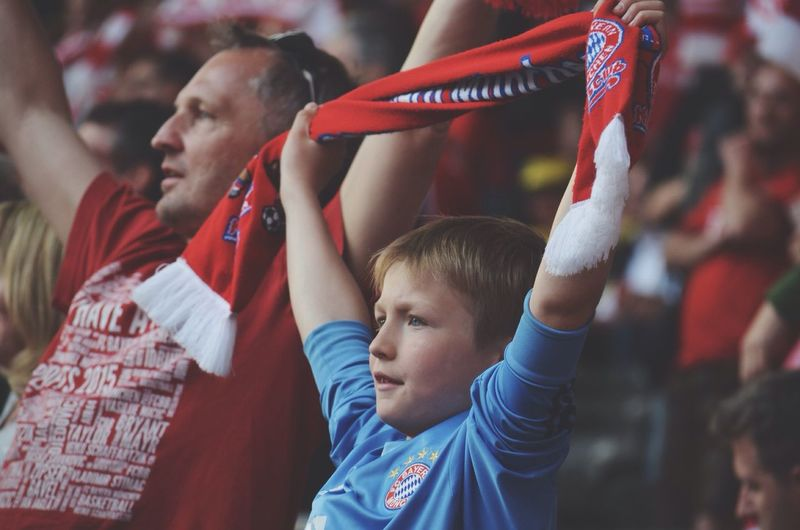 Father and son cheering at stadium