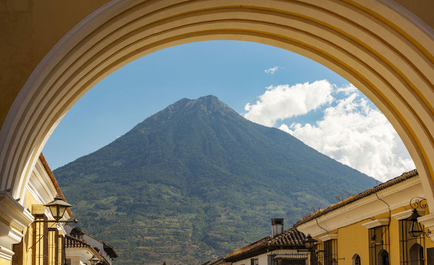 Volcan de Agua looms high behind the city of Antigua, Guatemala in Central America Mountain Architecture Sky Built Structure Arch Nature Building Exterior No People Day Building Scenics - Nature Cloud - Sky Mountain Range Window Beauty In Nature Outdoors Travel Destinations Travel Environment Guatemala Antigua Guatemala Volcano