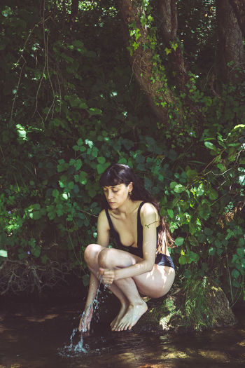 Woman sitting by tree in forest