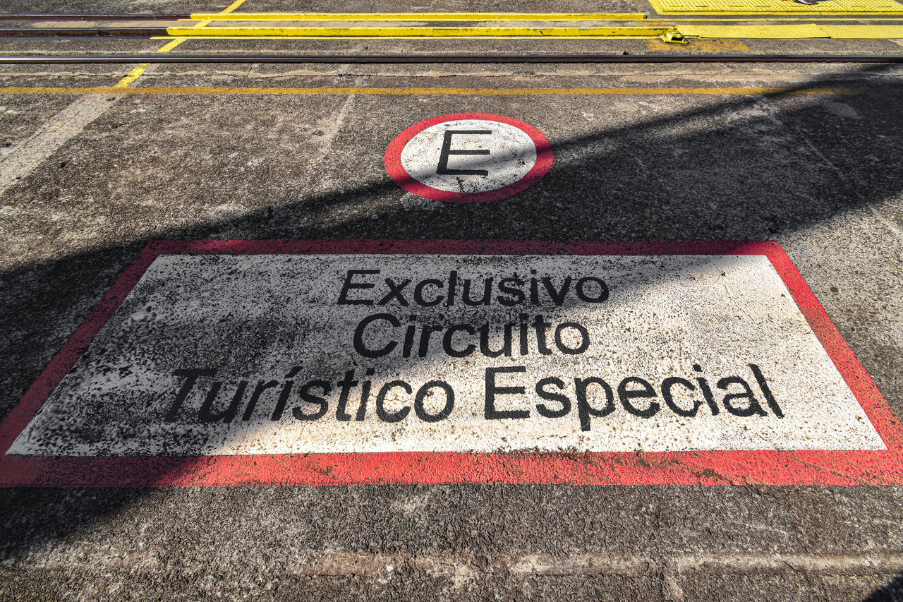 road, text, sign, communication, transportation, western script, day, street, high angle view, no people, competition, city, track and field, marking, road marking, asphalt, outdoors, sport, symbol, sports race
