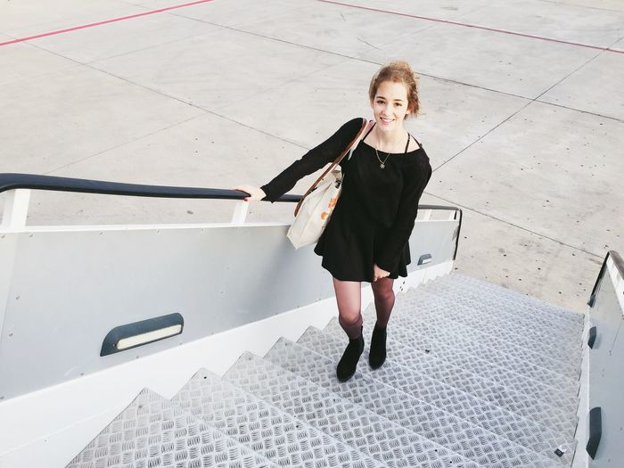 High angle view portrait of woman standing on staircase of airplane at runway
