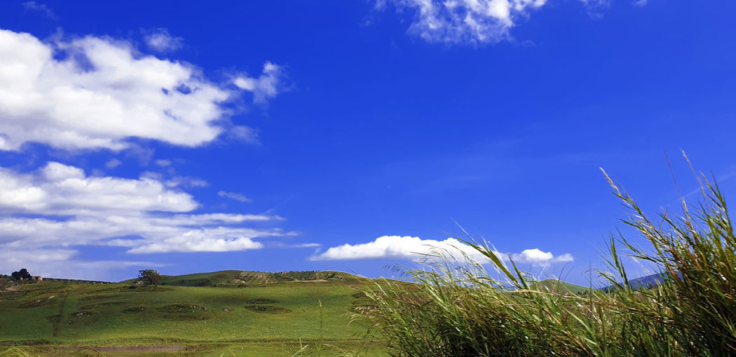 Low angle view of land against blue sky