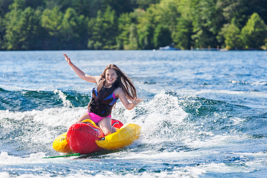 Laughing young girl speeds across a lake, hands in the air, on an inflatable on a summer day Wave Balance Cheerful Day Fun Kneeling Lake Leisure Activity Life Vest One Person Outdoors Smiling Tubing Water Water Sports