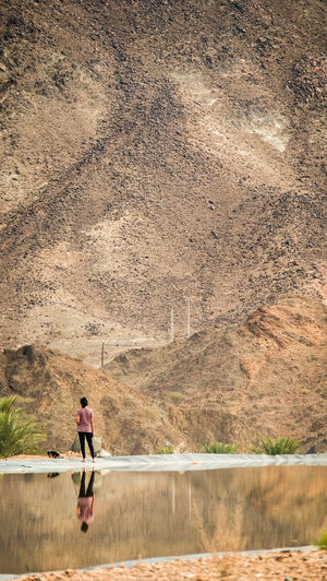 A young female teenager walking with a small dog in the mountains beside a clear mirror lake in Hatta, United Arab Emirates One Person Water Full Length Day Nature Mountain Outdoors Adult Lake Real People Lifestyles Beauty In Nature Leisure Activity Men Scenics - Nature Sitting Casual Clothing Tranquility Contemplation Reflection Walking Physical Activity Dog Exploring Wandering
