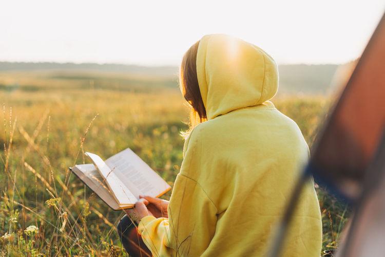 Rear view of woman wearing hood reading book on field