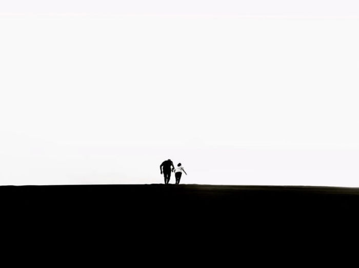 Silhouette people walking against clear sky