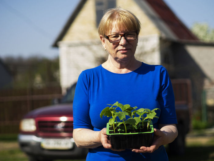 Senior caucasian woman is holds a container with cucumber seedlings. Seedlings Senior Women Caucasian Holds Container Cucumber Glasses Front View Eyeglasses  One Person Real People Focus On Foreground Waist Up Lifestyles Day Casual Clothing Holding Built Structure Architecture Standing Nature Building Exterior Plant Portrait Outdoors