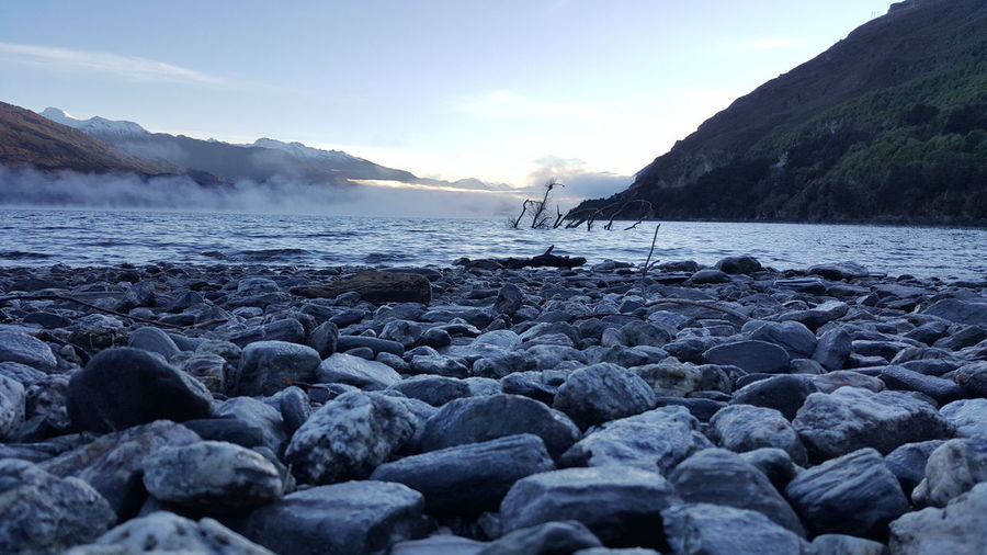 Surface level of pebble beach against the sky
