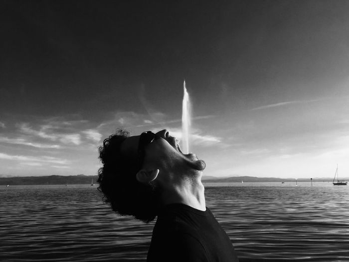 Optical Illusion Of Man Spraying Water From Mouth Against Sky