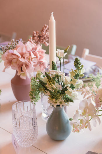 Flowering Plant Flower Table Plant Vase Nature Decoration No People Indoors  Freshness Vulnerability  Fragility Close-up Candle Beauty In Nature Flower Arrangement Pink Color Still Life Glass White Color Flower Head Bunch Of Flowers Purple Bouquet