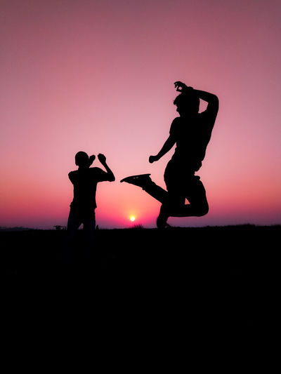 Silhouette Boy Jumping Against Sunset