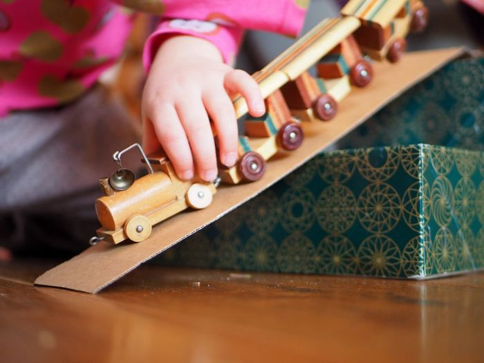 Human Hand Hand Table Human Body Part Wood - Material One Person Indoors  Real People Playing Leisure Activity Skill  Childhood Holding Women High Angle View Selective Focus Close-up Midsection Child Floral Pattern Toy Train Toytrain Ramp Play Boxes