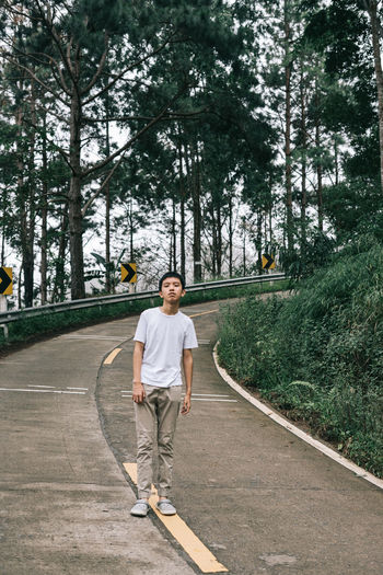 Full length portrait of boy standing on country road