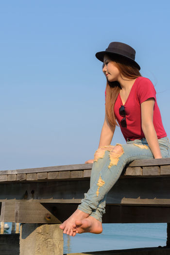 Full length of woman wearing hat sitting against clear blue sky