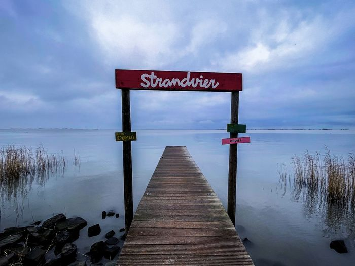 Warning sign on pier over lake against sky