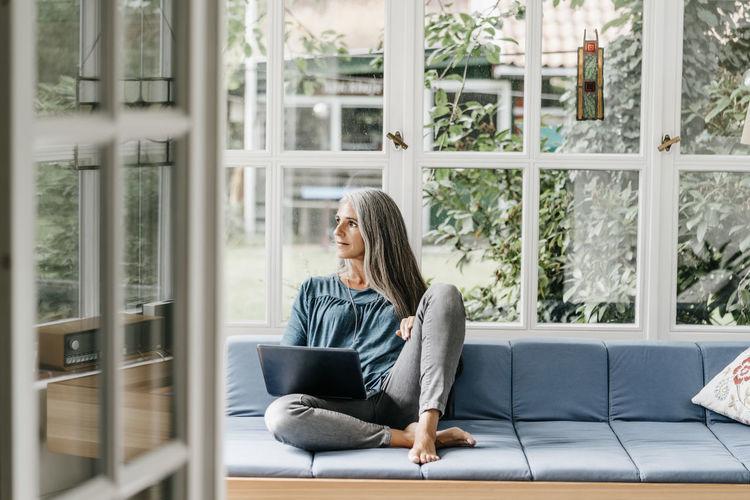 Full length of woman sitting on window